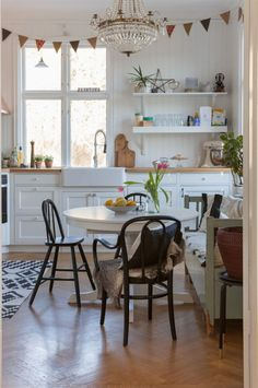 Lantlig stil. Vitt kök i lantlig stil med köksluckor med speglar och pärlspont på väggarna. Kristallkronan har Malin ärvt av sin farmor och farfar. Vimplarna har Malin gjort av inslagningspapper.