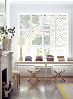 long table, stacked books, windows