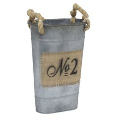Offering a rustic finishing touch to your decor, this metal bucket showcases rope handles and jute plaque detail.   Product: Bucket