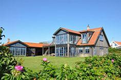 farm style Båstad house, big lawn, wood siding, blue window frames