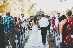Bride and father of the bride walking down the aisle at a rustic outdoor ceremony.