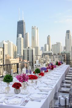 Downtown Chicago skyline photo -Public Chicago Hotel rooftop terrace! HMR Designs - Red roses glass chargers, ghost chairs -Gorgeous wedding rehearsal dinner picture by Chicago wedding photographer: Nakai Photography http://www.nakaiphotography.com wedding photographer langham