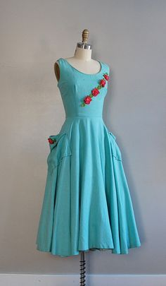Adorable turquoise 50s dress with rhinestones and red roses details.