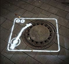 street art record player using a manhole cover as the turntable