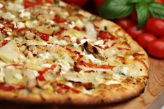 Homemade Tuscan Pizza: Pomodoro tomato sauce, pizza mozzarella, cheddar, spicy chicken breast, roasted garlic, fresh spinach, sun dried tomatoes and feta.