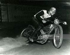 A rider broad slides through a corner on an Indian motorcycle during a 1920s-era race.