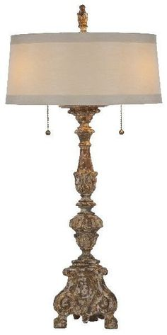FREE SHIPPING IN THE US. USE CODE LOVE10OFF FOR 10% OFF YOUR ENTIRE PURCHASE.  Aidan Gray took their gilded inspired candlestick and turned it into a lamp with a narrow horizontal shade. The base is heavily distressed revealing the gesso and natural wood underneath. The lamp is accompanied by a silk cream-colored shade. Wattage: 100W (2) Switch Type: Chain Pull