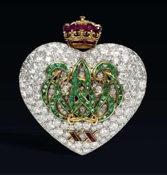 """""""For their 20th anniversary, the duke of Windsor gave the duchess a heart-shaped diamond brooch with an emerald pattern script 'W' and 'E' intertwined and a ruby crown on the top. Edward always regretted that Wallis was never bestowed the designation of Her Royal Highness, so the crown was a part of their lifelong love code spoken in jewelry."""" (1957, Cartier)"""