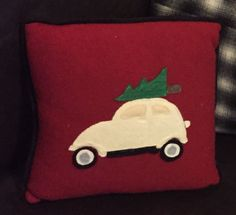 Emily's 2016 Christmas pillow. A VW Bug ( in Jacob's color) with Christmas tree on top is appliquéd onto a cranberry red cashmere wool, and edge trimmed with black wool piping. Reverse side in cream colored wool.