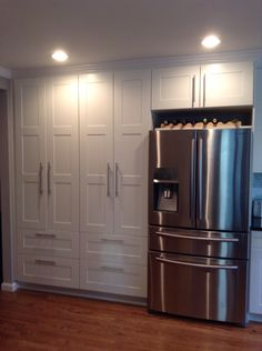 Double white ikea pantry. Samsung stainless steel French door refrigerator with dual zone drawer. Wine rack above fridge