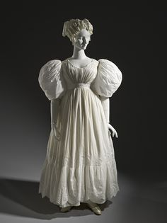 A circa 1830 English summer dress of a thin cotton material decorated with cutwork and embroidery. Romantic Era