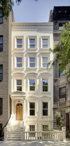 townhouse with different window mouldings, keep it simple with monochromatic white exterior