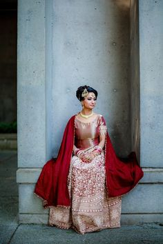 Elegant Indian bride in a gold and red Indian wedding lehenga.