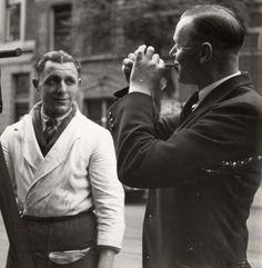 Vishandel, Straathandel, Hollandse nieuwe. Rotterdamse haringhandelaar op straat met een klant. Nederland, Rotterdam, 1936.