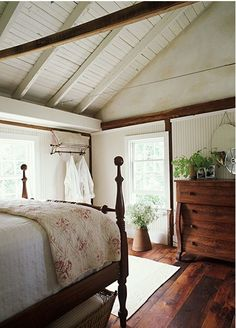 Cottage bedroom with charm: antique poster bed, dark floors, white walls, vaulted ceiling, faded floral duvet.