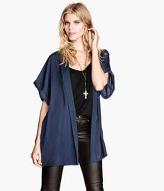 Blue short kimono in matte, silk-look woven fabric with contrasting lapels. Short, wide sleeves with sewn cuffs. No buttons.