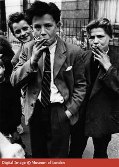 Roger Mayne photographed these young boys in North Kensington. Wearing oversized draped jackets and quiffed hair, they emulate the Teddy boy fashion of the 1950s Breaking from convention, teenage youths embraced the casual and affordable American-influenced style and culture. Production Date: 1956 ID no: MoL_IN15272 Maker: Mayne, Roger