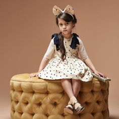 Sitting pretty  we love our flocked spot polka dot dress trimmed with velvet shoulder bows and paired with our matching hairband.  #polkadot #partydress #girls fashion