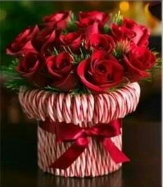 Christmas decor~ Candy cane vase! Put a rubberband around the vase, stick candy canes until the whole vase is covered, then tie a ribbon to cover the rubberband.