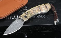 "William Henry B09 Golden Hornet - Mammoth Tooth, Damascus and Gold Koftgari.  Limited edition of only 10 individually numbered knives. The B09 Golden Hornet is a combination of fossil mammoth tooth inlay, 24k gold koftgari and a damascus steel blade. The William Henry B09 Golden Hornet upscale folding knife has a button lock and thumb stud inlaid with smokey quartz stone gems. This B09 Golden Hornet models features a sterling silver lanyard bale, braided brown leather lanyard with stainless steel metal beads, and matching brown leather ClipCase for safe carry and easy access. The damascus steel blade on this knife is hornets nest pattern; hand forged by blacksmith artisan Mike Norris. A unique serial number is engraved into the blade and every knife includes a Certificate of Authenticity and upscale wood presentation box.  MAKER: William Henry Knives BLADE SIZE: 2.06"" TOTAL SIZE: 5.06"" BLADE MATERIAL: Hornets Nest Pattern Damascus by Mike Norris HANDLE: Fossil Mammoth Tooth BOLSTERS: Blued tool teel with 24k gold koftgari  WEIGHT: 1.7 oz."