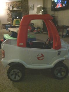 DIY Ghostbusters car...spray paint for plastic(red and white), masking tape(for stickers and precise edging), painters plastic, four grocery sacks(for the wheels), and two ghostbuster stickers off ebay...you'll need two coats of white paint but only one coat of red. Very cheap, one of a kind, and it only takes half a day.