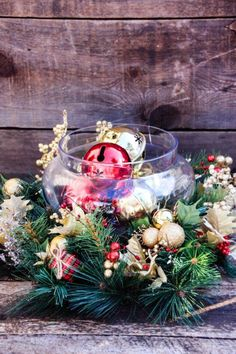 This is a quick and simple way to make a stunning centerpiece for your Christmas dinner table. From your local craft store, you'll need a pine wreath, red and gold jingle bells, berry brush, two mini red berry stems, four poinsettia balls, and a clear glass apothecary jar.