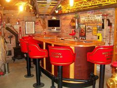I've always been a fan of brick, wood and industrial lighting. In contrast with the bar and awesome gold leafed chairs, this fire-man cave looks great!