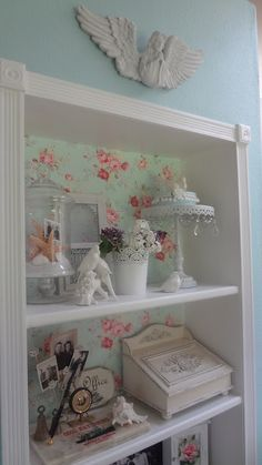 Built-in shelf - trimmed out in moulding with medallions at the corners - fabric backing for contrast - DIY shelves between studs bookshelf - could use wallpaper instead of fabric - could also be done with a nook.