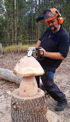 Myles Larden from Mad Hatter Mushrooms carving wood mushrooms for garden settings.