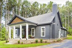 A cross-gable roof sits atop this storybook bungalow plan, with shake siding accents adding texture to the front porch. A brick skirt completes the de.