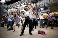 """Elderly people exercise with wooden dumbbells during a health promotion event to mark Japan's """"Respect for the Aged Day"""" at a temple in Tokyo's Sugamo district."""