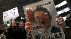 An anti-nuclear protester holds a placard depicting a defaced picture of Japan's Prime Minister Shinzo Abe during a rally near the parliament building in Tokyo, Japan, March 11, 2016. © Toru Hanai