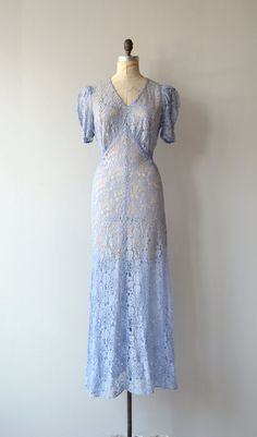 Vintage 1930s periwinkle lace gown with puff shoulder sleeves, soft V neckline, open back with fabric covered buttons, bias construction and back belt. --- M E A S U R E M E N T S --- fits like: medium shoulder: 16 bust: 41 waist: 30 hip: up to 44 length: 60 brand/maker: n/a condition: tears in the lace at the arm seams, seen in last photo, sold as is! To ensure a good fit, please read the sizing guide: http://www.etsy.com/shop/DearGolden/policy ✩ more vi...