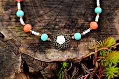 """The combination of aqua glass beads and coral faceted beads accented with small white pearl beads are accompanied by brass square spacers and a beautiful filigree with a white flower.The necklace is 18"""" long with a vintage brass lobster clasp"""