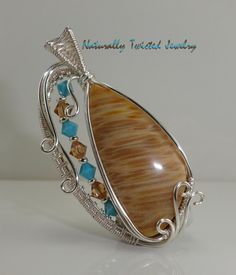 This beautiful handmade Palmwood cabochon is artistically wrapped with Swarovski Crystals and Fine Silver Plated wire and measures approximately 53mm