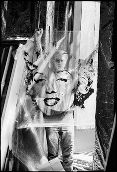 This 1964 image is Warhol Holding Marilyn Acetate I. Images of Andy Warhol and Robert Indiana taken in the early 1960s by fine art photographer William John Kennedy will be on display for a pop-up event on the heels of Art Basel.