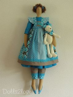 This beautiful handmade doll has a body which is based on a Tilda pattern. The cloths are designed and made by me. This lovely doll is wearing a dress made from turquoise fabric. The dress has puffed sleeves and the skirt has a ruffle. Under her dress she wears taupe spotty overknee