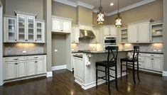 Off white kitchen cabinets, wood floors, gray counters, travertine backsplash