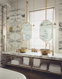 We're swooning over this London Bathroom design by Maddux Creative,  which we recently stumbled upon on Pinterest.   (Via)  Lined with deeply veined Arabescato marble, this gorgoeus bathroom is  outfitted with brass vessel sinks and fixtures, as well as floating  mirrors. Further adding to th