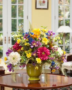 This just picked from the garden centerpiece is resplendent with bright silk zinnias, delphiniums, cosmos and daisies not to mention a number of other varieties of flowers. Arranged in a green ceramic cache pot, this colorful design isn't afraid of being the brightest bulb in any room, but actually prefers being the focal in its surrounding. $199