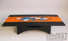 A stunning coffee table from the 1970's with hand painted tile top and glass fibre base.