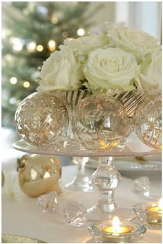 elegant center piece. clear & gold ornaments around white roses. throw in some crystal-like accessories around the roses. voila!
