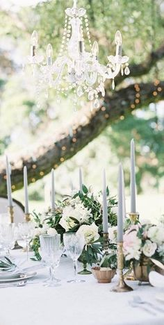 greenery, white, and grey elegant outdoor reception with romantic candlelight and crystal glassware