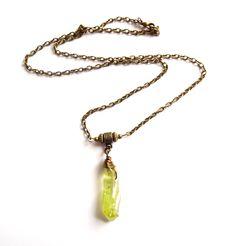 Halsband i brons med en grön aura kvarts kristall.  Hängets storlek: 4-5cm Längd: 56cm  Eftersom det är en naturprodukt så kan kristallens storlek och färg