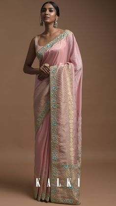 """How about a modern twist to our ol' favourite saree? We present to you this ravishing salmon pink banarasi saree with turq accented floral embroidery, encrusted with dazzling sequin and kundan work. And while we're at it, also check out these enticing drop earrings from our newest accessories edit """"Bahaar"""" Style Tip: Dramatic winged eyeliner with a loose mid parted ponytail will make you look effortlessly chic. Saree Tassels Designs, Pattu Saree Blouse Designs, Dupion Silk Saree, Banarasi Sarees, Latest Indian Saree, Indian Sarees Online, Saree Floral, Lehenga Style, Blue Saree"""