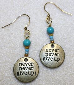 "Handcrafted by Teal Palmetto, LLC. A great phrase to live by!! Silver-tone pewter disk charms are engraved with ""never never give up!""  They are complemented with silver-tone metal beads and silver fish hook ear wires. A great phrase to live by!! Gold-tone pewter disk charms are engraved with ""never never give up!"" They are complemented with teal and gold glass accent beads.  This pair has gold-tone fish hook ear wires.  Price: $14"