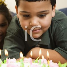 iPHOTOS.com - Royalty Free Photo of a Boy Looking Down Wishfully at Lit Candles of a Birthday Cake With Girl Peeking in Over His Shoulder