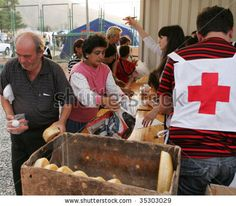 GORI, GEORGIA - SEPTEMBER 8: Red Cross workers distribute food at a refugee camp on September 8, 2008 in Gori, Georgia. - stock photo