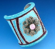 This gorgeous, 3 inch polymer clay cuff bracelet was made on an aluminum blank, in a shade of aqua  The focal piece is a lovely antique silver filigree flower, layered with a pink Swarovski crystal center MEMBER - Alexis Studio Design