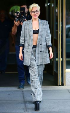 Lady Gaga suits up in her own way, pairing oversized square specs with a striped grey ensemble.